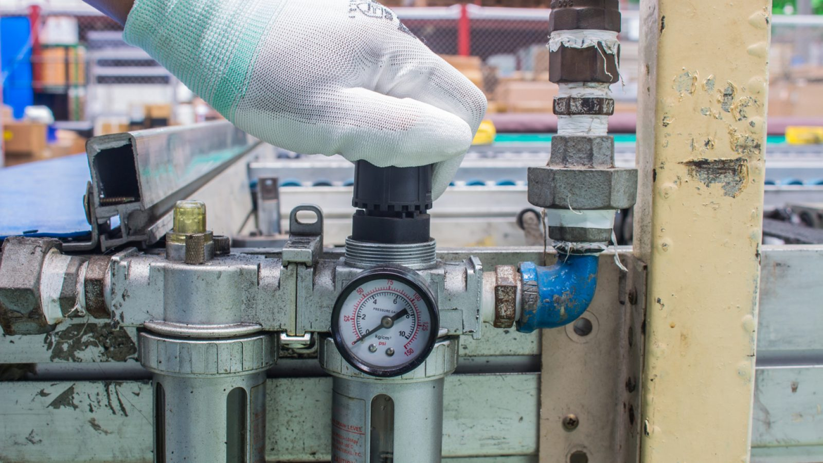 The hand of technician adjust the pressure setting of the wind on regulator. In the pneumatic system